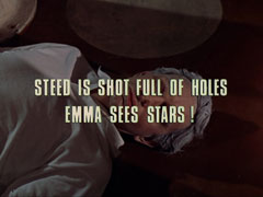 subtitle card: white all caps text with black dropshadow to the left reading 'STEED IS SHOT FULL OF HOLES      EMMA SEES STARS!' superimposed on a close-up of Cosgrove lying dead on the floor with his hair turned grey